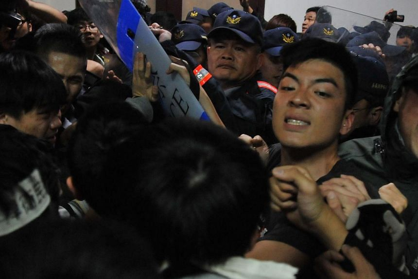 Protesters scuffle with police at the Executive Yuan in Taipei early on March 24, 2014, during a protest following Taiwan President Ma Ying-jeou's refusal to scrap a contentious trade agreement with China. -- PHOTO: AFP