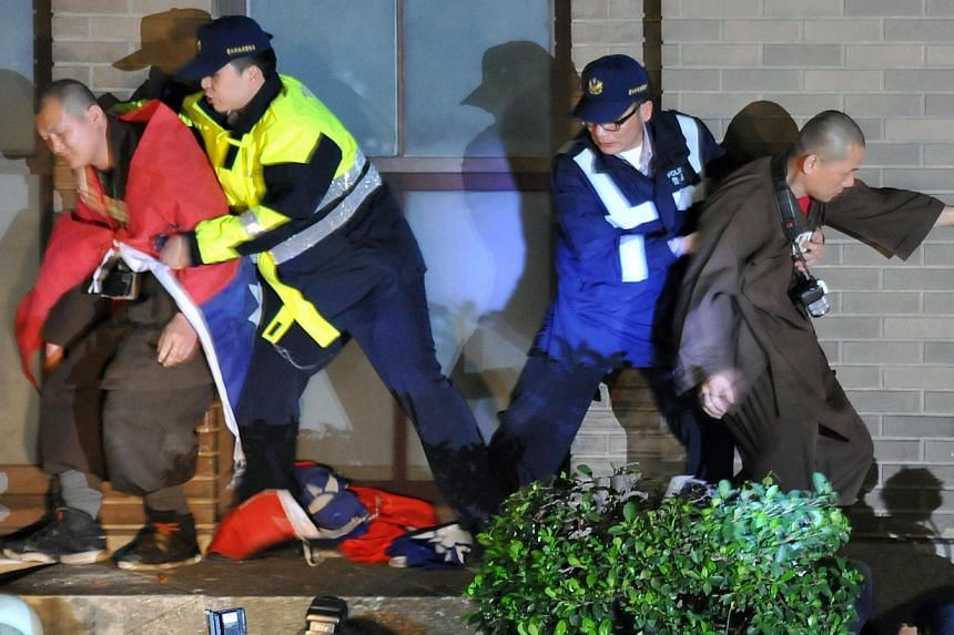 Police officers (centre) remove protesters at the Executive Yuan in Taipei early on March 24, 2014, during a protest following Taiwan President Ma Ying-jeou's refusal to scrap a contentious trade agreement with China. -- PHOTO: AFP