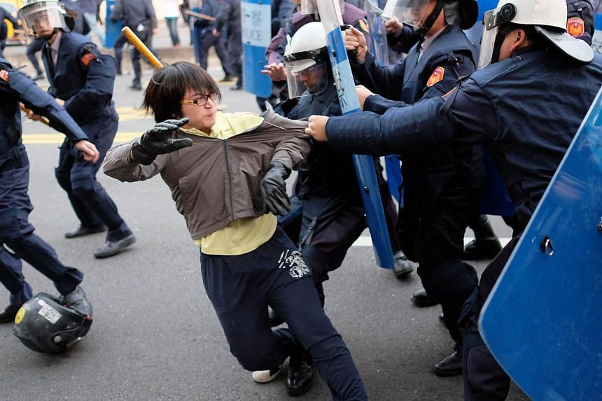 Protesters scuffle with police officers outside the Executive Yuan during a demonstration in Taipei on early March 24, 2014, following Taiwan President Ma Ying-jeou's refusal to scrap a contentious trade agreement with China. -- PHOTO: AFP