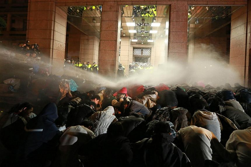 Protesters are sprayed with a water cannon during a demonstration outside the Executive Yuan in Taipei early on March 24, 2014, following Taiwan President Ma Ying-jeou's refusal to scrap a contentious trade agreement with China. -- PHOTO: AFP