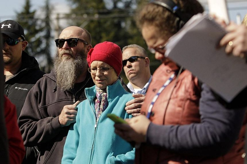 Concerned citizens listen as Washington Governor Jay Inslee addresses the media in Arlington, Washington as rescuers search for people still missing from a landslide on March 23, 2014. -- PHOTO: REUTERS