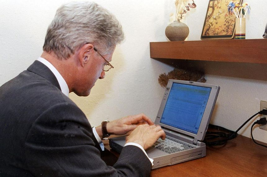 Then US President Bill Clinton preparing an e-mail on Nov 6, 1998 from the home of a friend in Arkansas. Mr Clinton sent the first email ever sent by a US president -- to senator and astronaut John Glenn aboard the space shuttle Discovery . The lapto