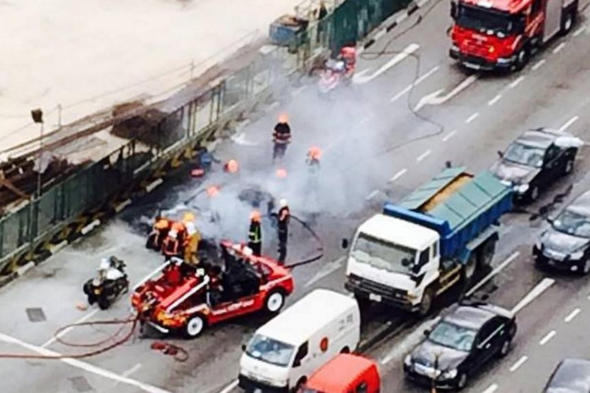 A TransCab taxi burst into flames along Woodlands Road near the Junction 10 shopping mall on Tuesday afternoon, causing a traffic snarl.-- PHOTO: GISELLE ONG