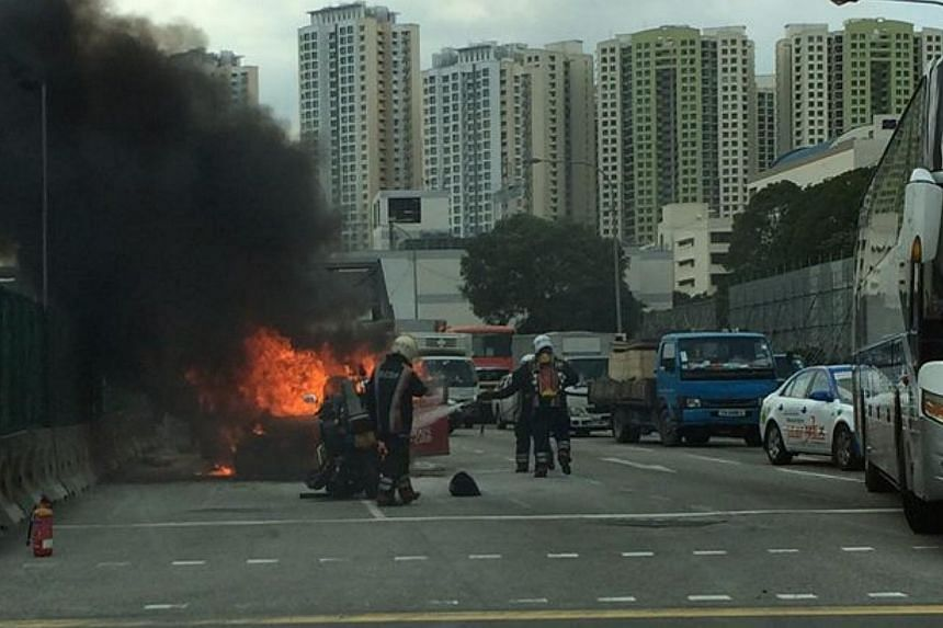 A TransCab taxi burst into flames along Woodlands Road near the Junction 10 shopping mall on Tuesday afternoon, causing a traffic snarl.-- PHOTO: FLORIAN GREBER