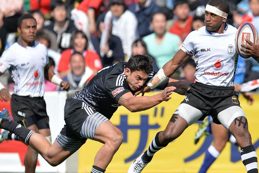Fiji's rugby sevens team (in white) in action against New Zealand in Tokyo on March 23, 2014. Fiji is threatening to boycott this year's Glasgow Commonwealth Games after being told its high-profile rugby sevens side cannot take part. -- PHOTO: AFP