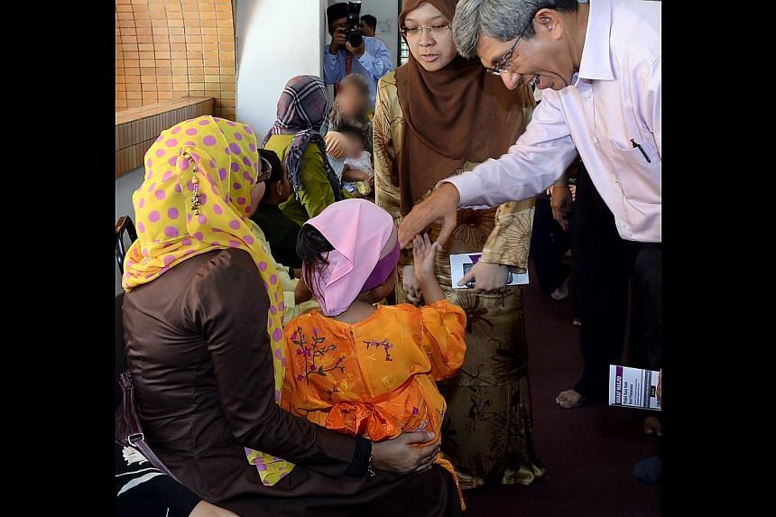 Dr Yaacob (right) speaking to beneficiaries who can now apply for aid at heartland sites, including the Al-Muttaqin mosque. With him is Ang Mo Kio GRC MP Intan Azura Mokhtar (middle). -- PHOTO: BERITA HARIAN