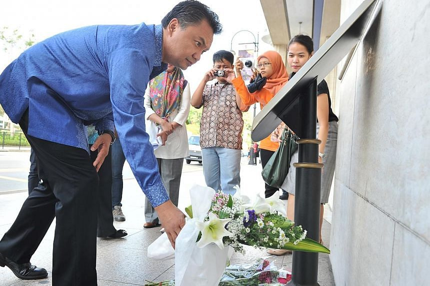 Young Indonesian leader Dino Patti Djalal laying flowers at MacDonald House on March 25, 2014, the site of a 1965 bombing by two Indonesian marines. -- PHOTO: LIM YAOHUI FOR THE STRAITS TIMES