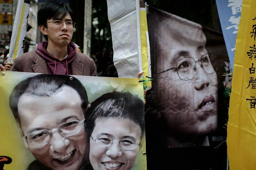 A demonstrator holds a banner before a march to the China Liaison office as they rally in support of Liu Xia (right, seen on banner), the wife of imprisoned Chinese dissident and Nobel Peace Prize winner Liu Xiaobo, in Hong Kong on March 7, 2014. The