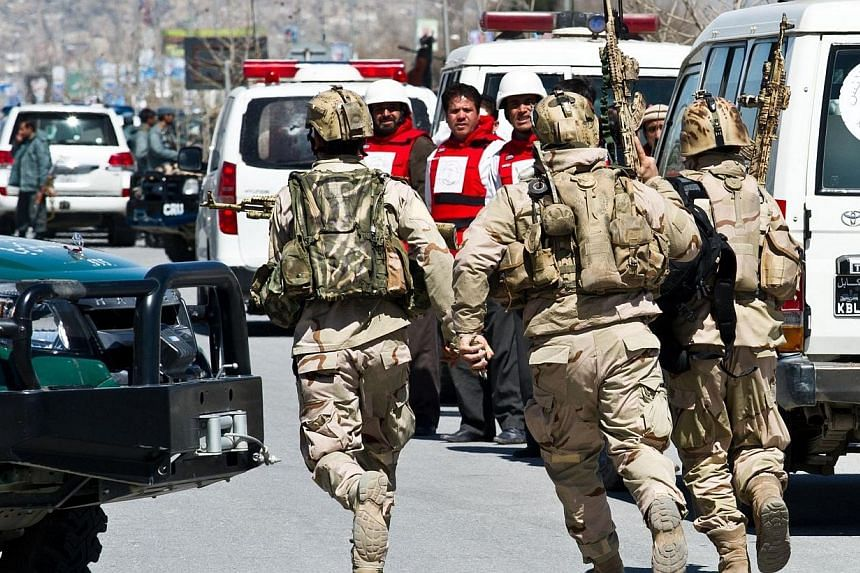 Emergency medical personnel wearing bullet proof vests watch as Afghan Special Forces troops rush towards an Afghan election commission office during an attack by militants in Kabul on March 25, 2014. Militants launched a gun and suicide attack on an