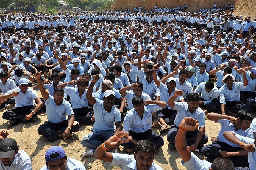 Toyota Kirloskar Motor Private Limited employees shout pro-labour union slogans as they gather near the facility after the company halted production at its two factories amid a labour dispute regarding wages on the outskirts of Bangalore on March 20,
