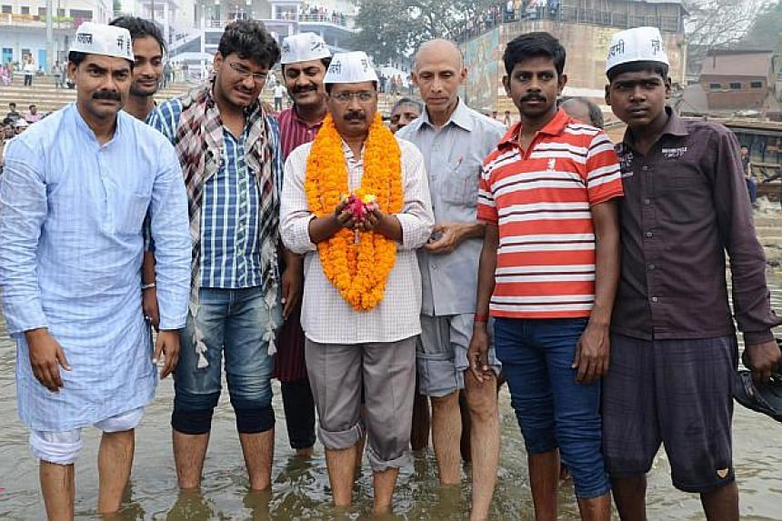 Indian head of the Aam Aadmi (Common Man) Party Arvind Kejriwal (C) poses for a photograph as he visits the river Ganges in Varanasi on March 25, 2014. The leader of a fledgling Indian anti-corruption party announced plans to stand against election f