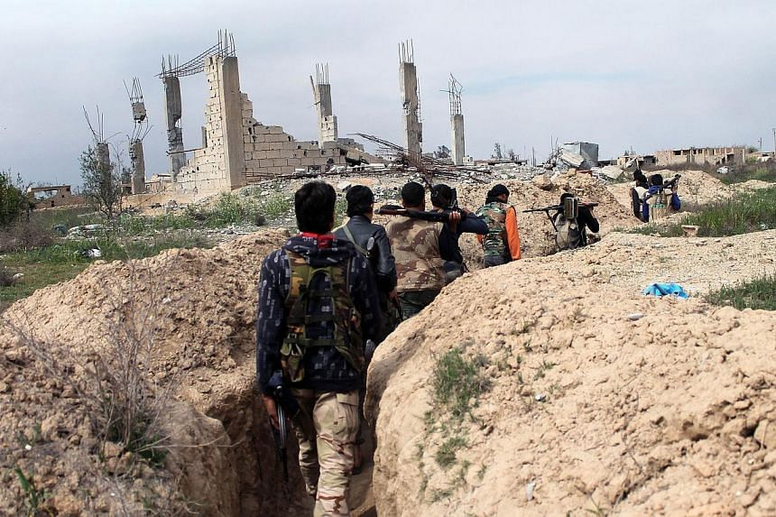 Rebel fighters carry their weapons as they walk along a trench in the northeastern city of Deir Ezzor as fighting with pro-regime fighters continues, on March 24, 2014.Saudi Arabia's crown prince said Tuesday, March 25, 2014, the international