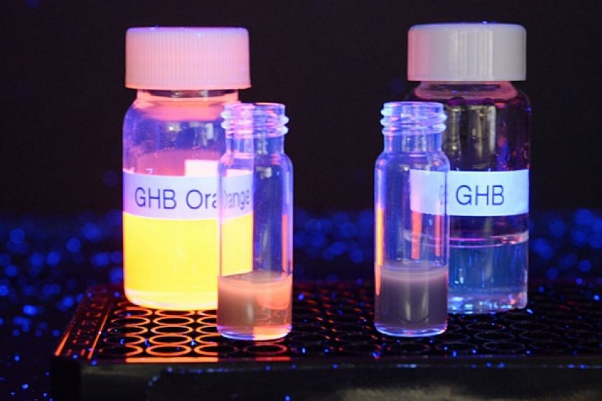 GHB Orange, the flourescent sensor for detecting date rape drug GHB (background, left), pictured under UV light with the drug GHB (background, right), and when it was mixed into redwine without GHB (left) and with GHB (right).-- ST PHOTO: