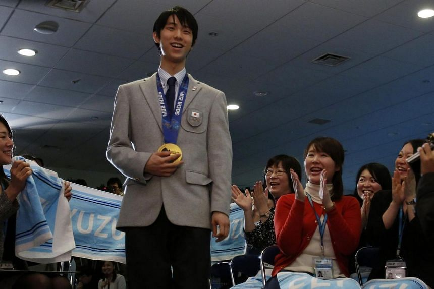 Japan's Olympic figure skating gold medallist Yuzuru Hanyu walks as employees of All Nippon Airways (ANA), a company he represents, welcome him during a ceremony to mark his homecoming at its headquarters in Tokyo on Feb 25, 2014.The pressure is on O