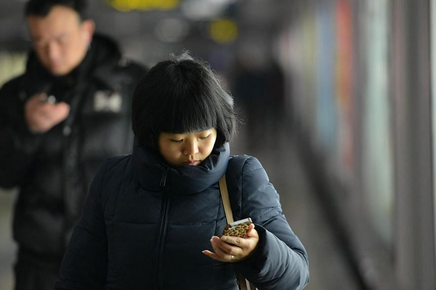 People use their mobile devices to communicate in a metro station in Shanghai on March 12, 2014. The Chinese authorities said on Tuesday, March 25, 2014, they have detained 1,530 people in a crackdown on the use of fake telecommunication base st