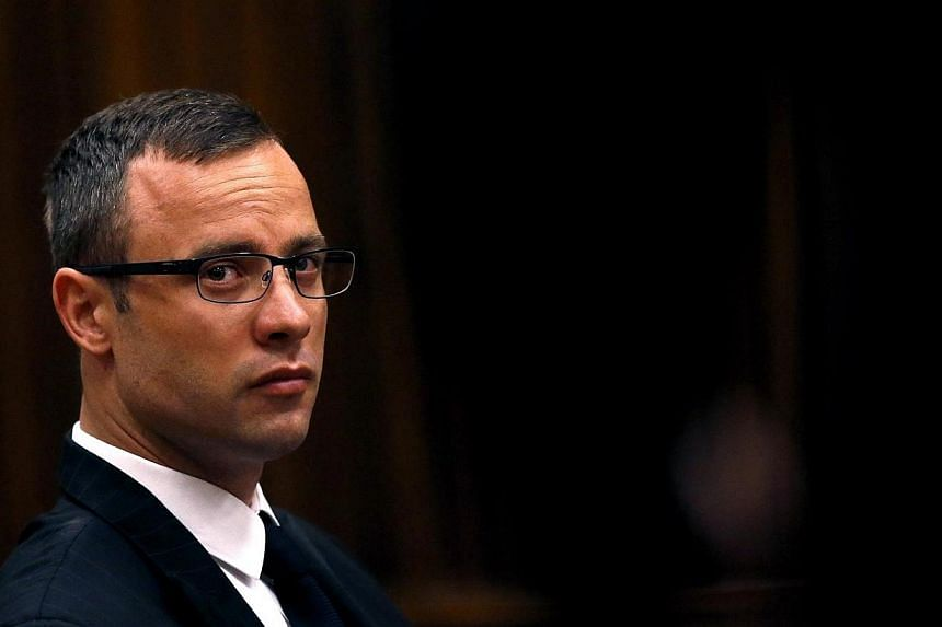 Olympic and Paralympic track star Oscar Pistorius sits in the dock ahead of his trial for the murder of his girlfriend Reeva Steenkamp, at the North Gauteng High Court in Pretoria on March 25, 2014. The defence in Oscar Pistorius's murder trial will