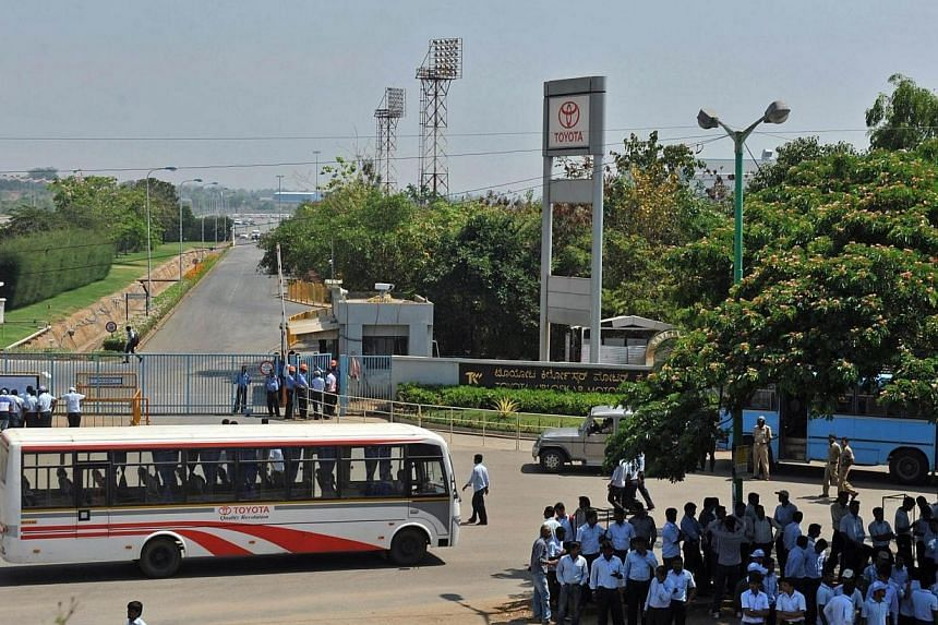 Toyota Kirloskar Motor Private Limited employees gather outside the facility after the company halted production at its two factories amid a labour dispute regarding wages on the outskirts of Bangalore on March 20, 2014.Japan's Toyota said in a