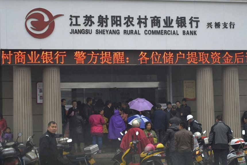 People gather in front of a branch of Jiangsu Sheyang Rural Commercial Bank, in Yancheng, Jiangsu province, March 25, 2014. Hundreds of people rushed to withdraw money from a branch of a small Chinese bank on Monday after rumours spread about its sol