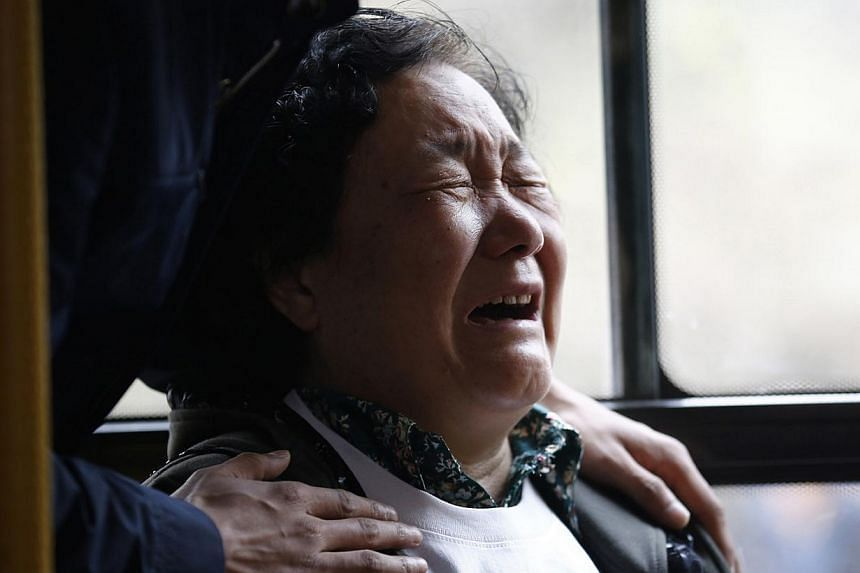 A family member of a passenger onboard Malaysia Airlines Flight MH370 cries on a bus before heading to the Malaysian embassy, outside Lido Hotel in Beijing, on March 25, 2014. -- PHOTO: REUTERS