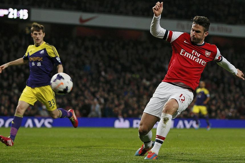 Arsenal's Olivier Giroud (right) scores during their English Premier League match against Swansea City at the Emirates stadium in London on March 25, 2014. -- PHOTO: REUTERS