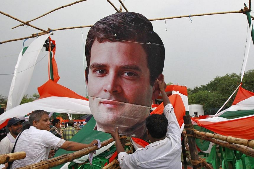 A worker from India's ruling Congress party holds a broken cut-out of Mr Rahul Gandhi, Congress party vice-president and son of Congress chief Sonia Gandhi, which was damaged in rain and thunder storm before the start of a party meeting ahead of the