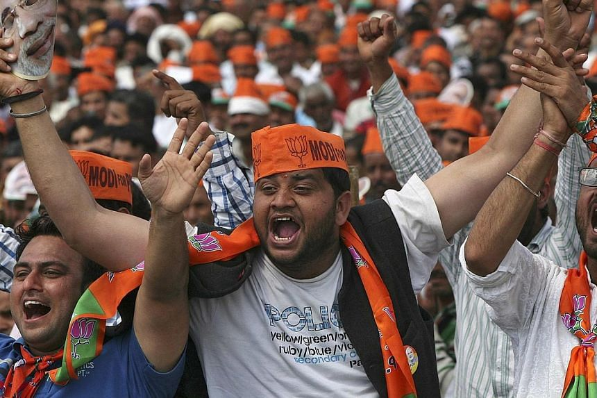 Supporters of Hindu nationalist Narendra Modi, prime ministerial candidate for India's main opposition Bharatiya Janata Party (BJP) and Gujarat's chief minister, cheer as they listen to Modi during a rally in Hiranagar March 26, 2014. India's opposit