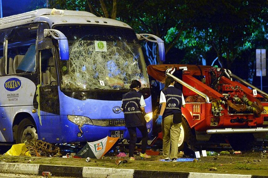 Police officers examining the wrecked private bus at the aftermath of the Little India riot in the early hours on Dec 9, 2013.With the conclusion of the committee of inquiry into the riot on Wednesday (26/03), the committee is expected to delib