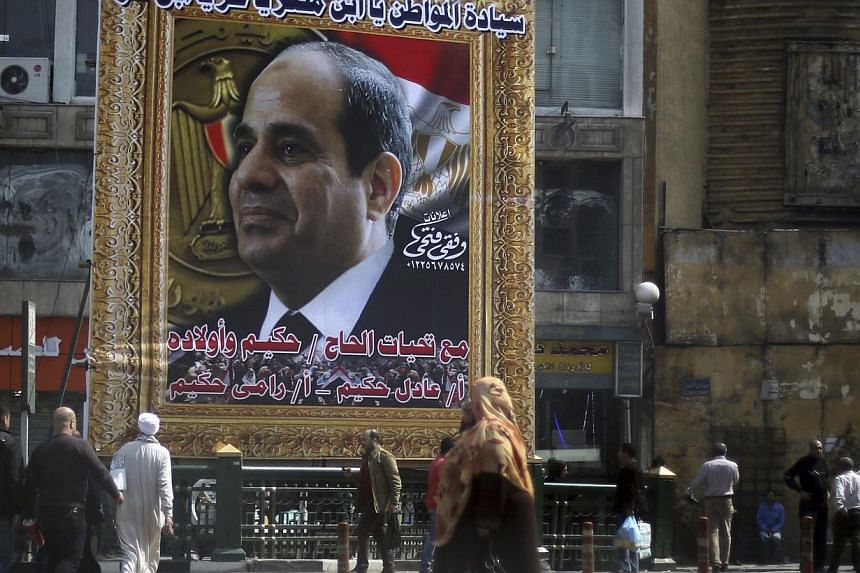 People walk past a banner for Egypt's army chief, Field Marshal Abdel Fattah al-Sisi, in downtown Cairo, March 24, 2014.Egypt's army chief, Field Marshal Abdel Fattah al-Sisi, met military leaders on Wednesday, March 26, 2014, to say he was res