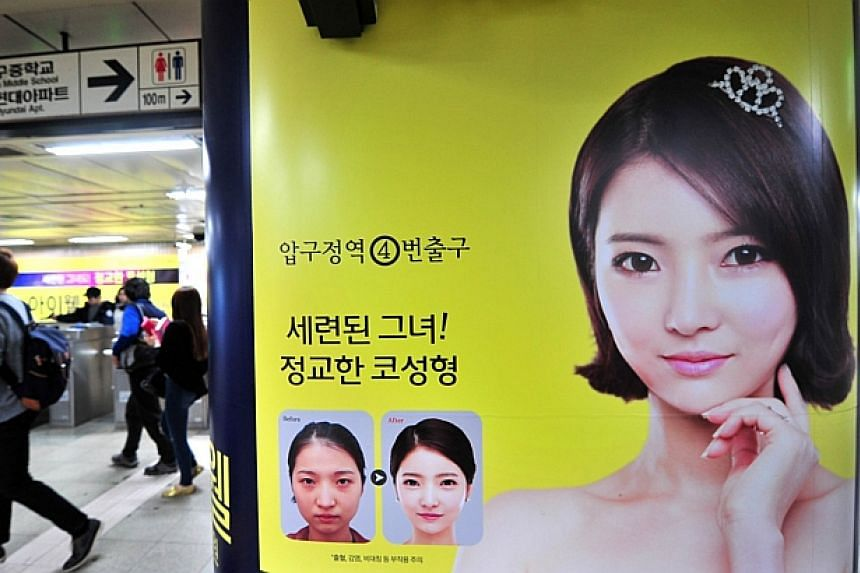 Pedestrians walk past an advertisement for plastic surgery clinic at a subway station in Seoul on March 26, 2014.-- PHOTO: AFP