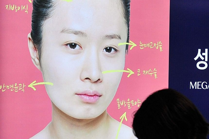 A pedestrian walks past an advertisement for plastic surgery clinic at a subway station in Seoul on March 26, 2014. -- PHOTO: AFP