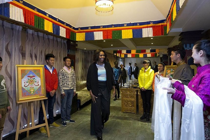 US first lady Michelle Obama (centre) is greeted by Tibetan students as they arrive at a Tibetan restaurant for lunch in Chengdu in southwest China's Sichuan province on March 26, 2014. MrsObama lunched at a Tibetan restaurant in China's Sichua
