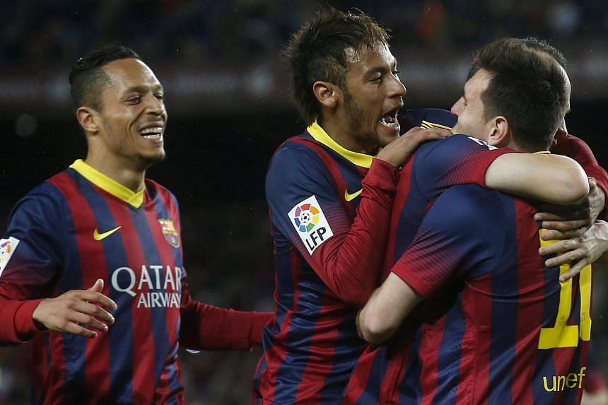 (From left) Barcelona's Adriano Correia), Neymar, Lionel Messi and Andres Iniesta celebrate a goal against Celta Vigo during their La Liga match at Camp Nou stadium in Barcelona on March 26, 2014. -- PHOTO: REUTERS