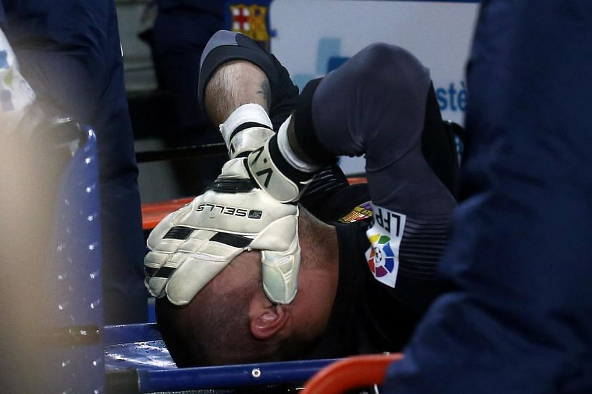 Barcelona's goalkeeper Victor Valdes being carried off on a stretcher after picking up an injury against Celta Vigo during their La Liga match at Camp Nou stadium in Barcelona on March 26, 2014. -- PHOTO: REUTERS