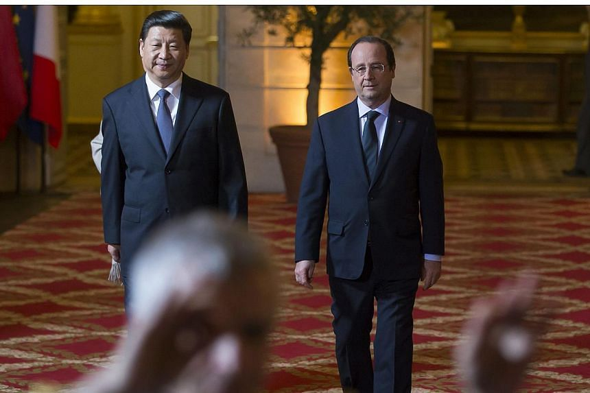 French President Francois Hollande (right) and Chinese President Xi Jinping (left) walk near the conductor of an orchestra before the State dinner held at the Elysee Palace in Paris on March 26, 2014. -- PHOTO: REUTERS