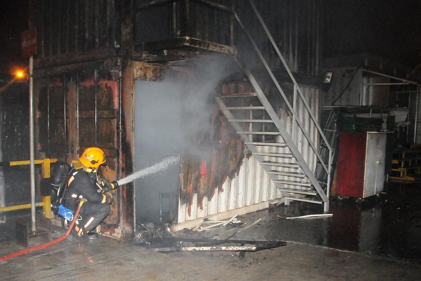 Firefighters putting out the fire at the Downtown Line 2 worksite in Little India on Wednesday night. -- PHOTO: SCDF
