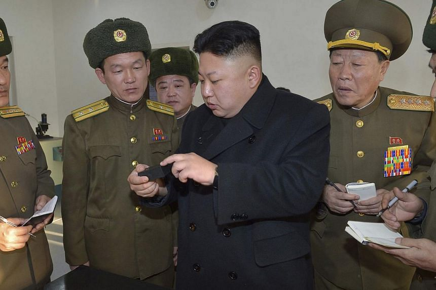 North Korean leader Kim Jong Un (centre) visiting a newly constructed factory producing bullets for competitive sports, as well as the Maeari Shooting Range, in this undated photo released by North Korea's Korean Central News Agency on Feb 12, 2014.