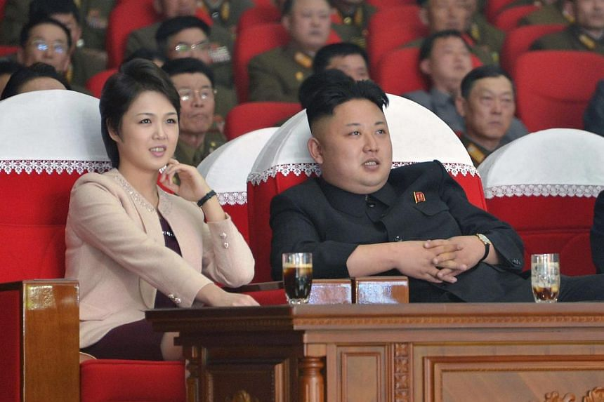 North Korean leader Kim Jong Un and his wife Ri Sol Ju watching a performance by the Moranbong Band at the April 25 House of Culture in this undated photo released by North Korea's Korean Central News Agency in Pyongyang on March 24, 2014. -- FILE PH