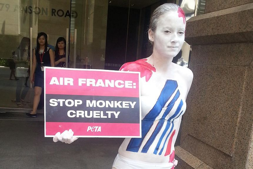Clad in nothing more than white underwear and covered with streaks of body paint, animal activist Ashley Fruno stood outside the Anson Road office of Air France on Thursday afternoon.-- ST PHOTO: AUDREY TAN