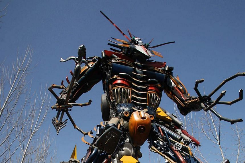 A man looking at several life-sized Transformer models on display in a yard in Jinan, east China's Shandong province on March 21, 2014.-- FILE PHOTO: AFP