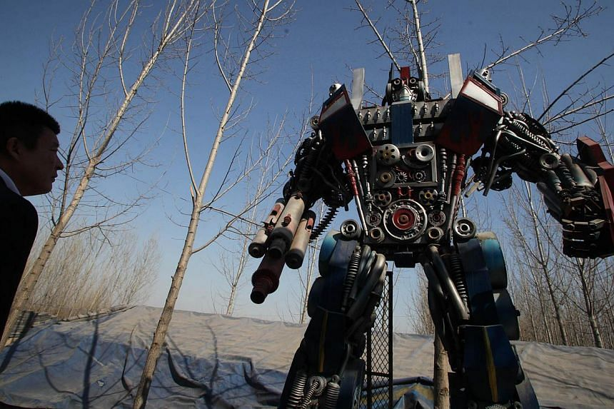 A man looking at a life-sized Transformer model on display in a yard in Jinan, east China's Shandong province on March 21, 2014. -- FILE PHOTO: AFP