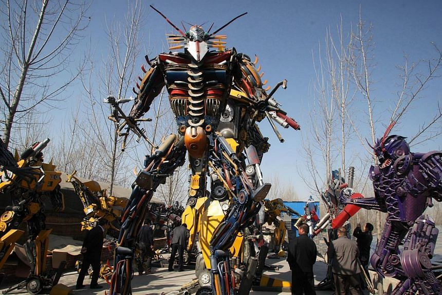 People looking at several life-sized Transformer models on display in a yard in Jinan, east China's Shandong province on March 21, 2014.  -- FILE PHOTO: AFP