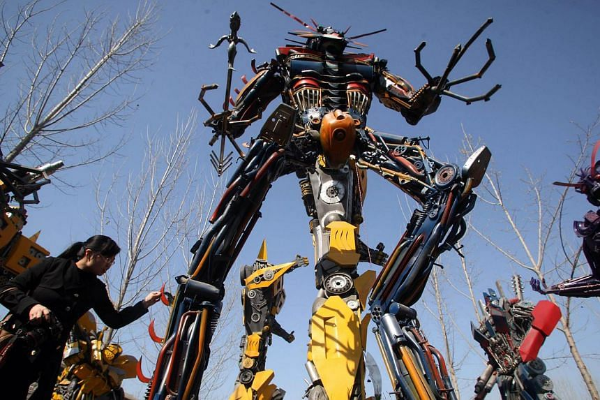 A woman looking at a life-sized Transformer model in a yard in Jinan, east China's Shandong province on March 21, 2014.  -- FILE PHOTO: AFP