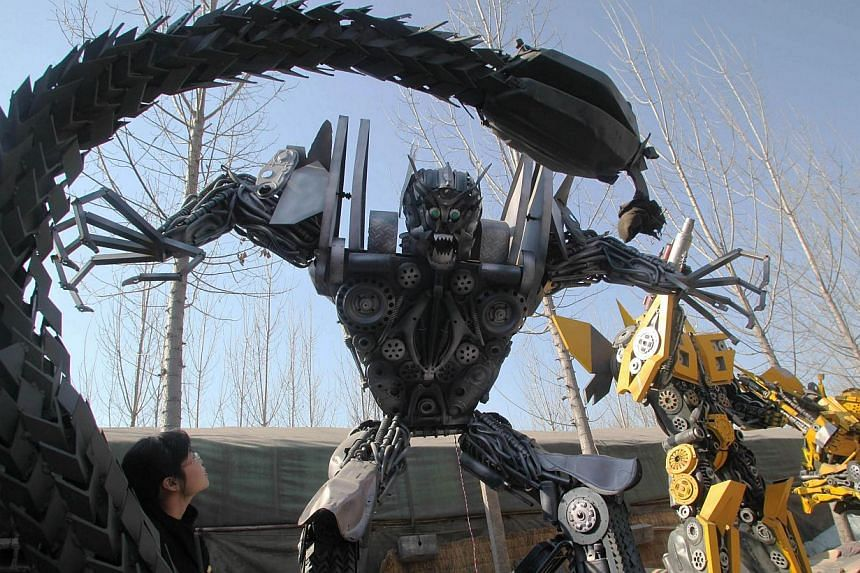 A woman looking at several life-sized Transformer models on display in a yard in Jinan, east China's Shandong province on March 21, 2014. -- FILE PHOTO: AFP
