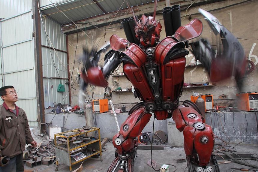 A man standing by a life-sized Transformer model on display in a yard in Jinan, east China's Shandong province on March 21, 2014.-- FILE PHOTO: AFP