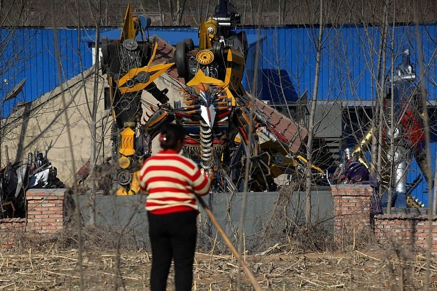 A woman looking at several life-sized Transformer models in a yard in Jinan, east China's Shandong province on March 21, 2014. -- FILE PHOTO: AFP