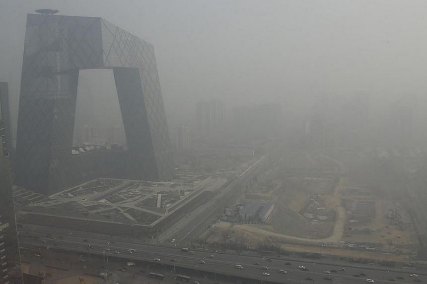 The China Central Television (CCTV) building is seen next to a construction site in heavy haze in Beijing's central business district, in this photo from Jan 14, 2013. China plans to move some administrative, research and healthcare facilities out of