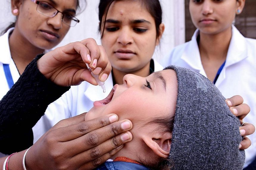 An Indian child receives polio vaccination drops from a medical volunteer during a National Pulse Polio Immunisation (PPI) programme in Amritsar on January 19, 2014.The World Health Organisation (WHO) declared India free of the crippling polio