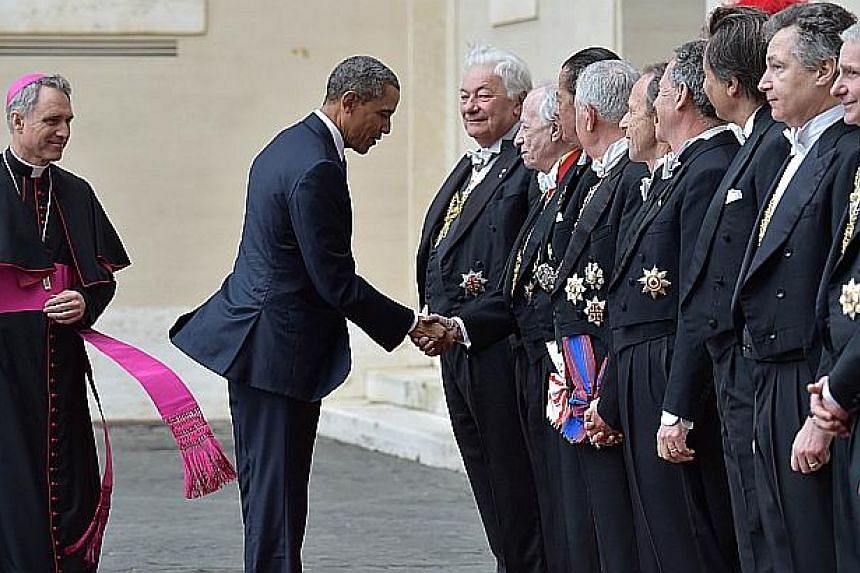 US President Barack Obama (centre) is welcomed by officials as he arrives for a private audience with Pope Francis on March 27, 2014 at the Vatican. -- PHOTO: AFP