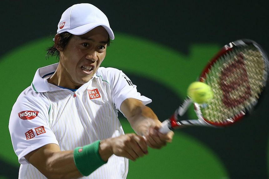 Kei Nishikori of Japan plays a backhand against Roger Federer of Switzerland during their quarter final round match during day 10 at the Sony Open at Crandon Park Tennis Centre, on March 26, 2014, in Key Biscayne, Florida. -- PHOTO: AFP