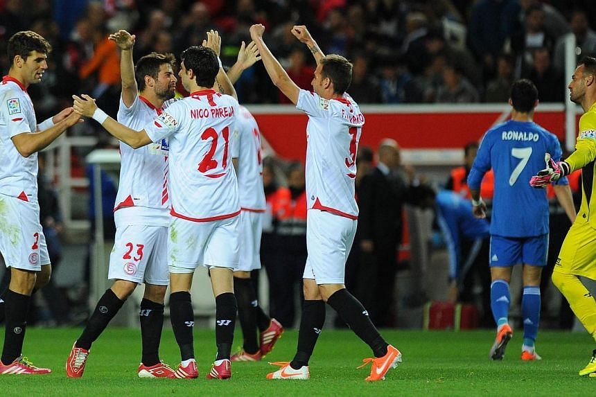 Sevilla's players celebrate after winning the Spanish league football match Sevilla FC vs Real Madrid FC at the Ramon Sanchez Pizjuan stadium in Sevilla on March 26, 2014. -- PHOTO: AFP
